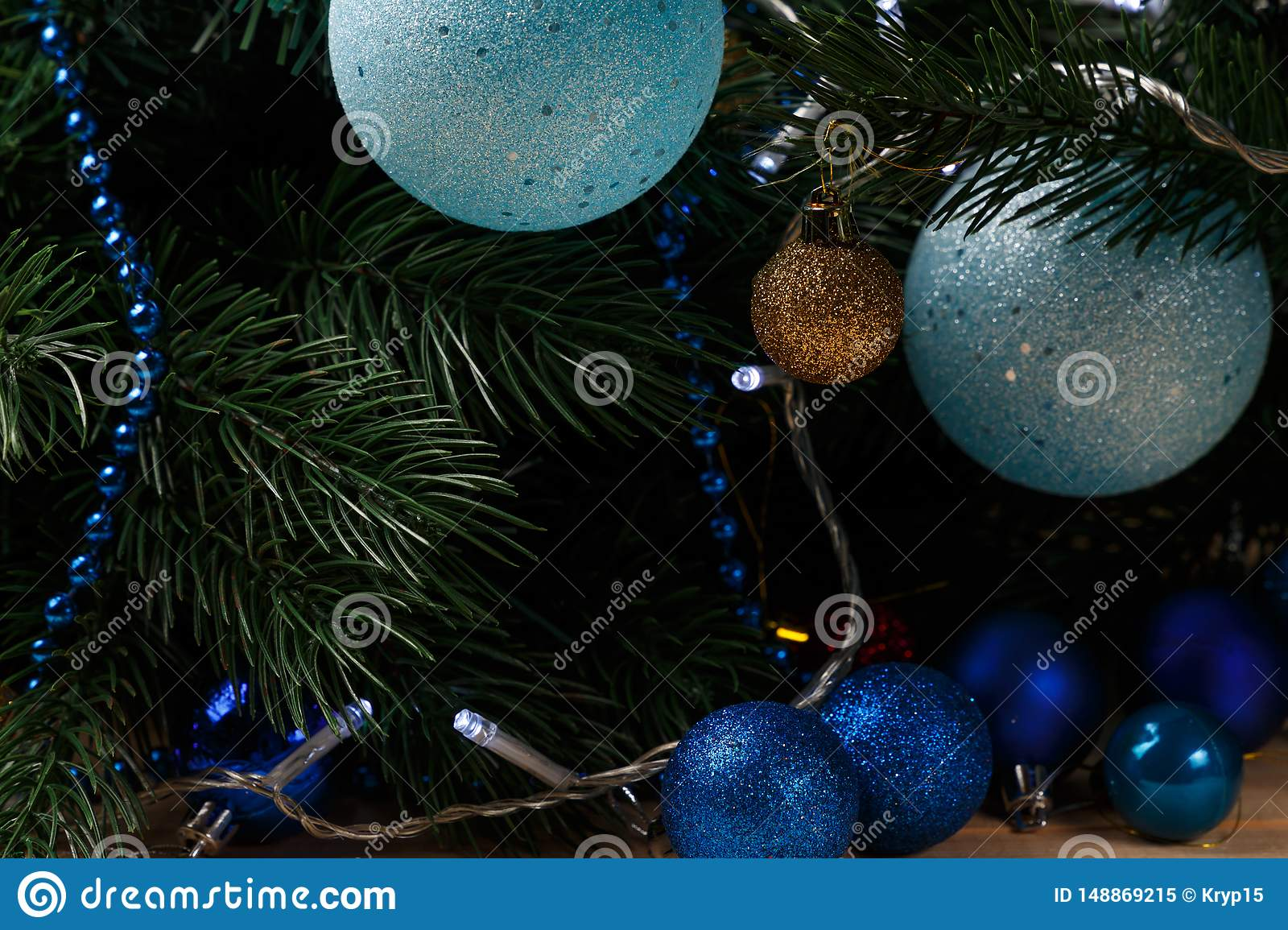 Christmas or New Year decoration background: fur-tree branches, colorful glass balls on black grunge background