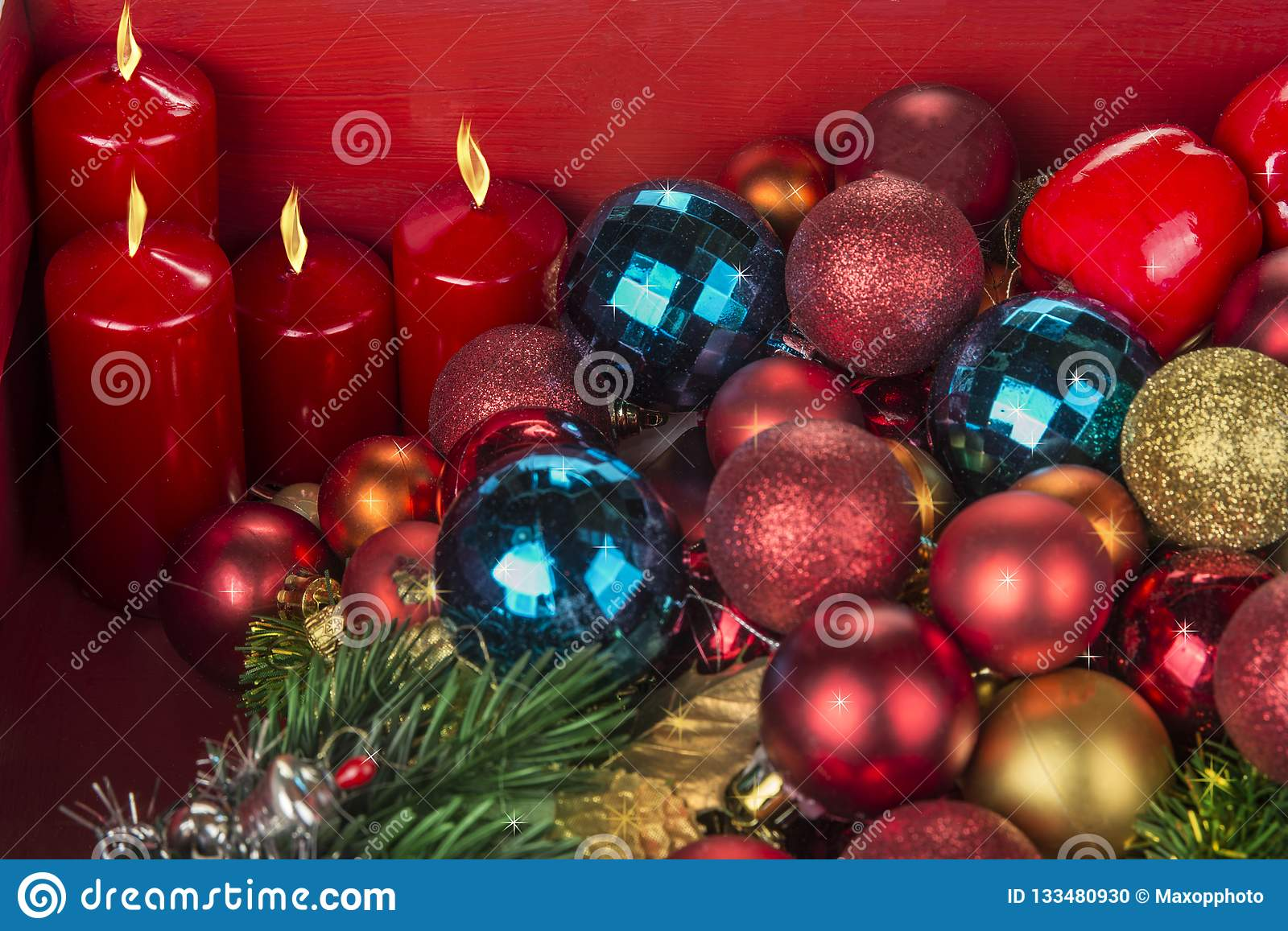 Christmas and New Year decoration balls and candels on red background.