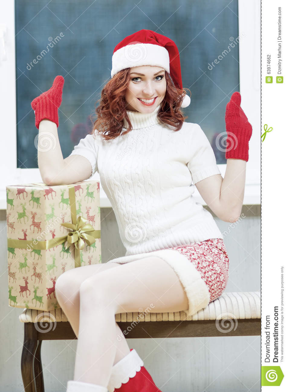 Christmas, New Year, X-Mas Concepts and Celebrations. Young Caucasian Santa Helper Girl With Big Present Box. Posing as Snow Maid