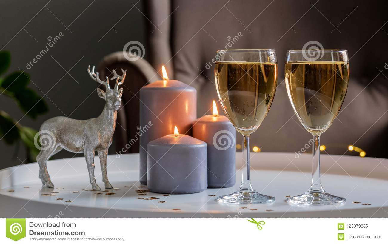 christmas and new year new years decor two glasses with champagne burning candles a christmas tree and a decorative statue of a deer on a white table