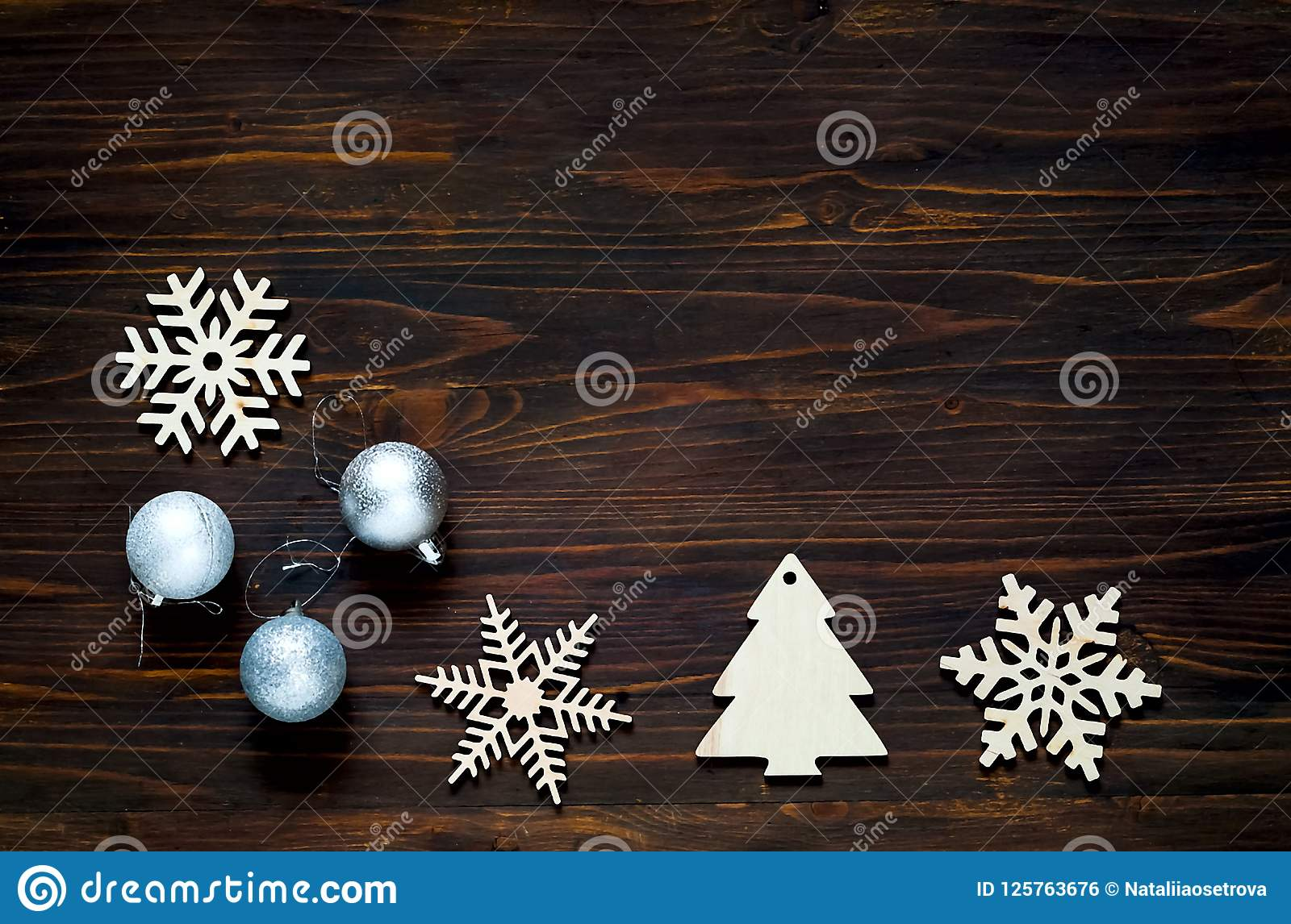 Christmas and New Year`s decor. Decorative wooden snowflakes and silver balls on wooden background, concept of New Year`s holiday