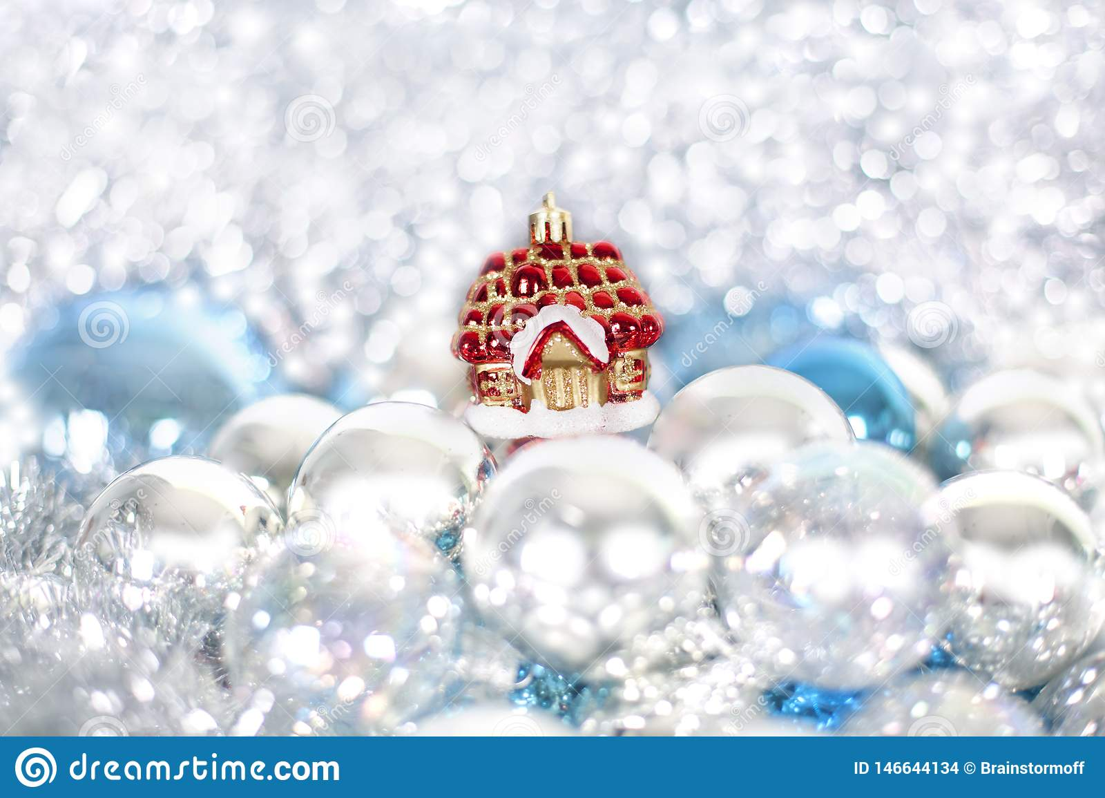 Christmas and New Year`s toy fairy tale red house in snowdrifts and snow of Christmas balls and tinsel in blue and white colors