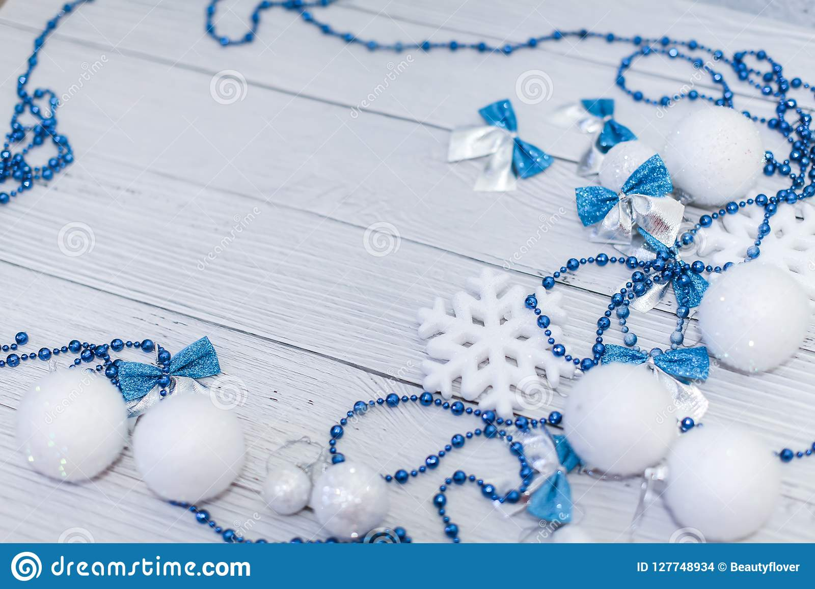 Christmas or newyear frame composition in silver white and blue colors with balls snowflake bows and beads on white wood