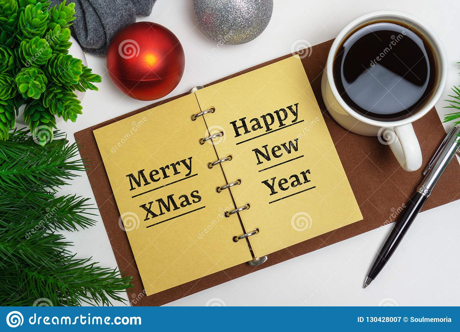 Christmas and Happy New Year on notepad with coffee and Christmas decorations.