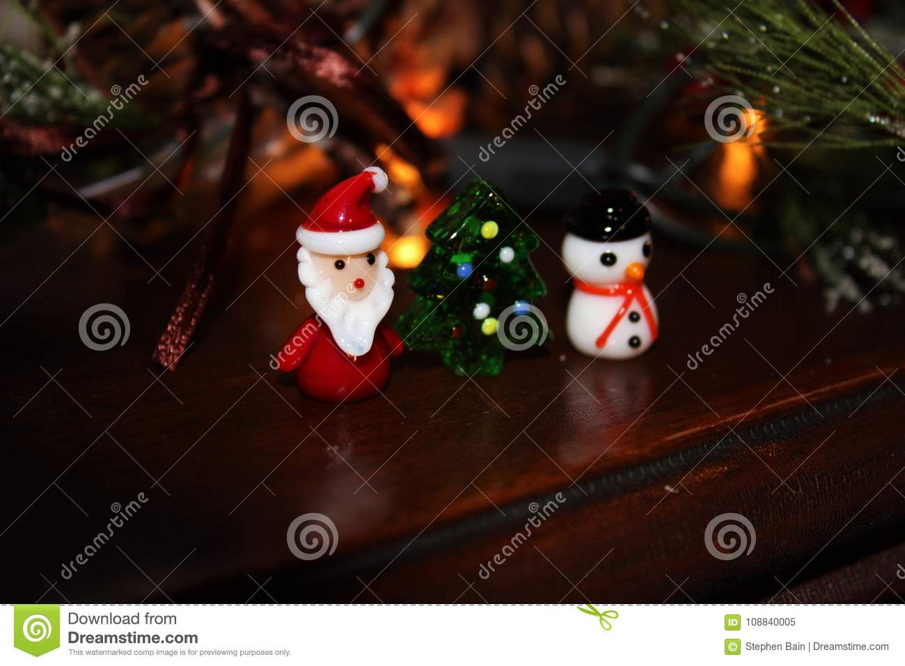download christmas ornaments sitting on dark wooden piano with fir bows lights and ribbons stock