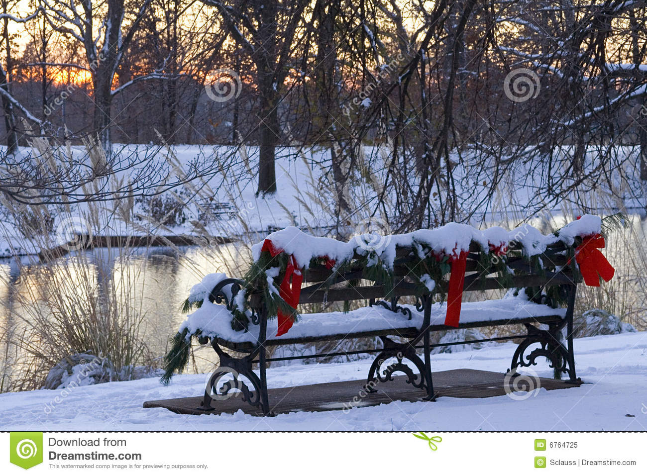 Old style wrought iron and wood park bench decorated with pine boughs ...