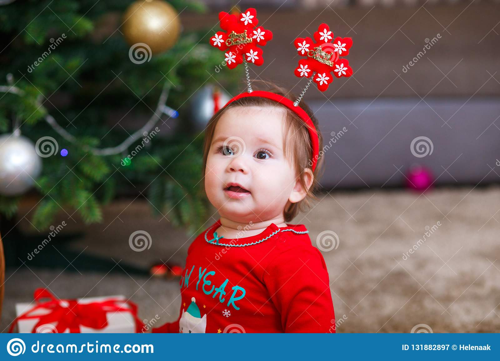 3b3962648f9 Christmas photo of infant in red cap. New Year`s holidays and Christmas tree