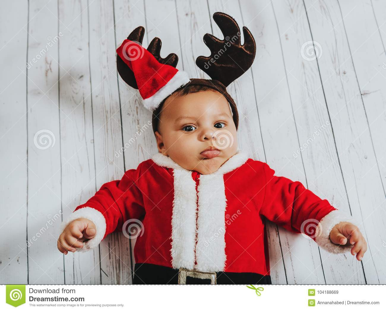 fb9bb2f1afa7 Christmas portrait of adorable baby boy lying on white background, wearing  Santa Claus` outfit and reindeer ears, top view