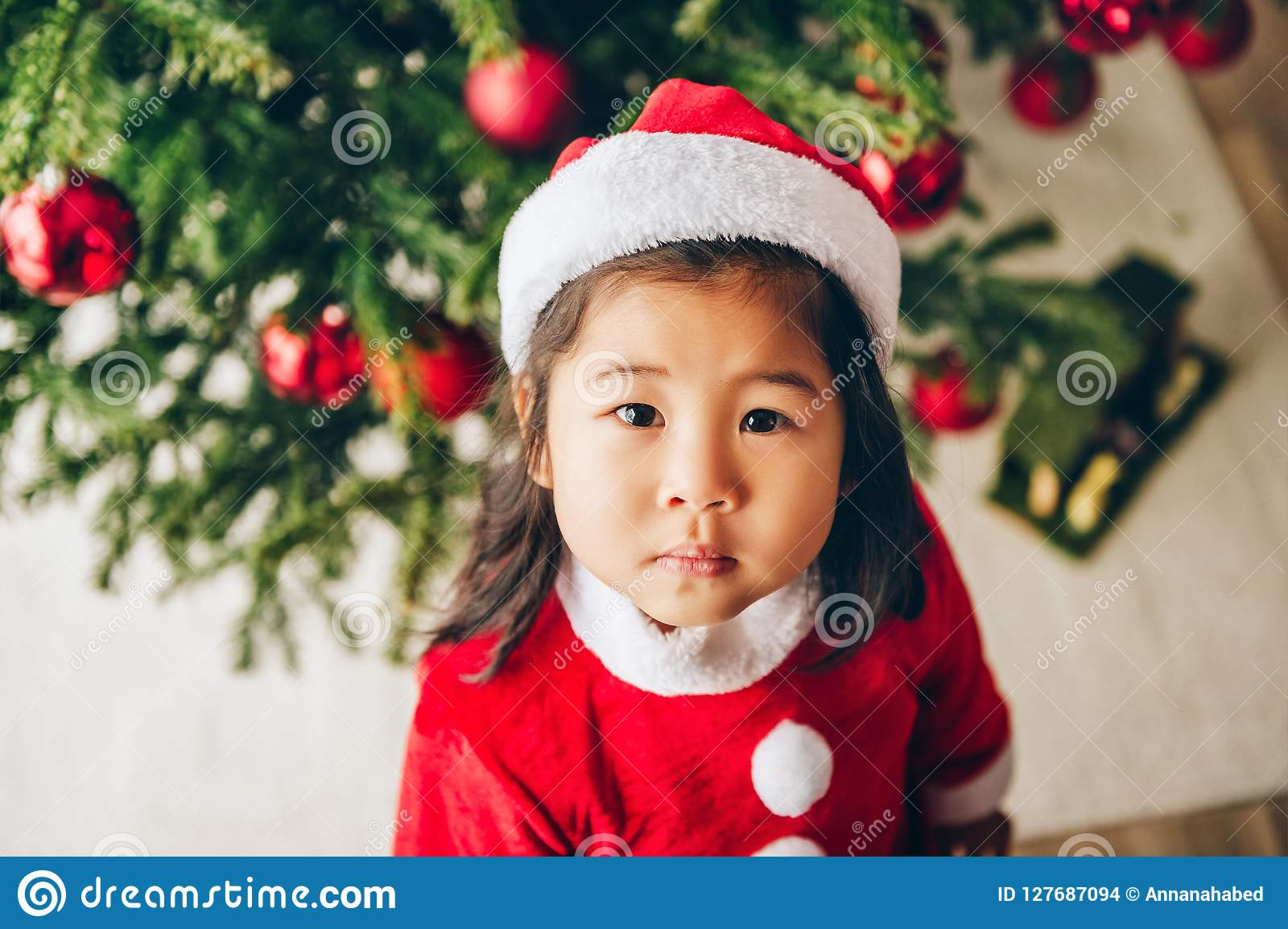 Christmas portrait of adorable 3 year old asian toddler girl wearing red Santa dress and hat