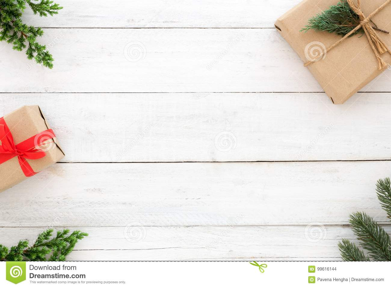 Christmas present gift boxes and fir leaves decoration rustic elements on white wood background