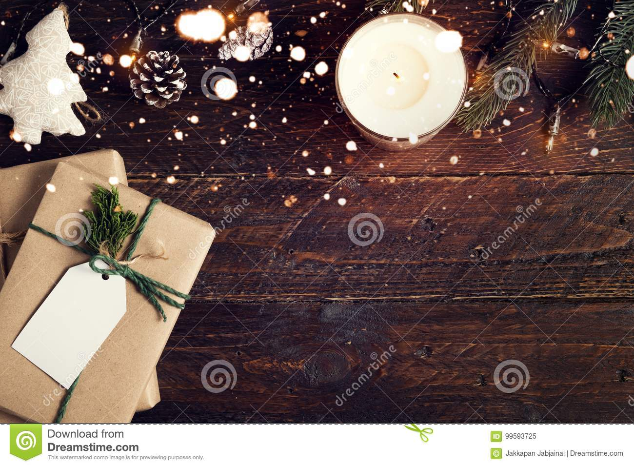 Christmas present gifts box and rustic decoration on vintage wooden background with snowflake.