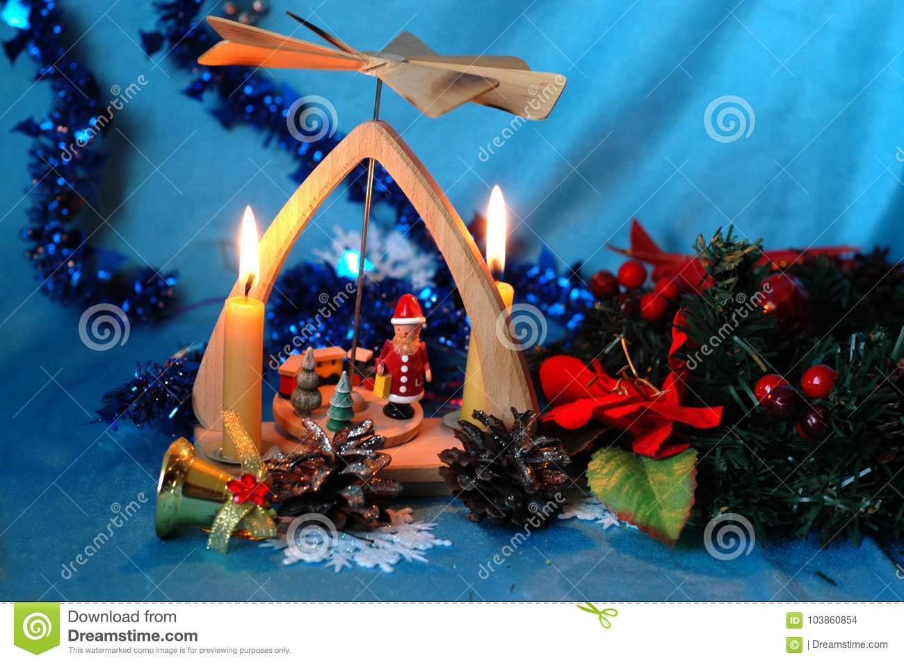 Christmas pyramid with candles, a wreath of fir branches and flo