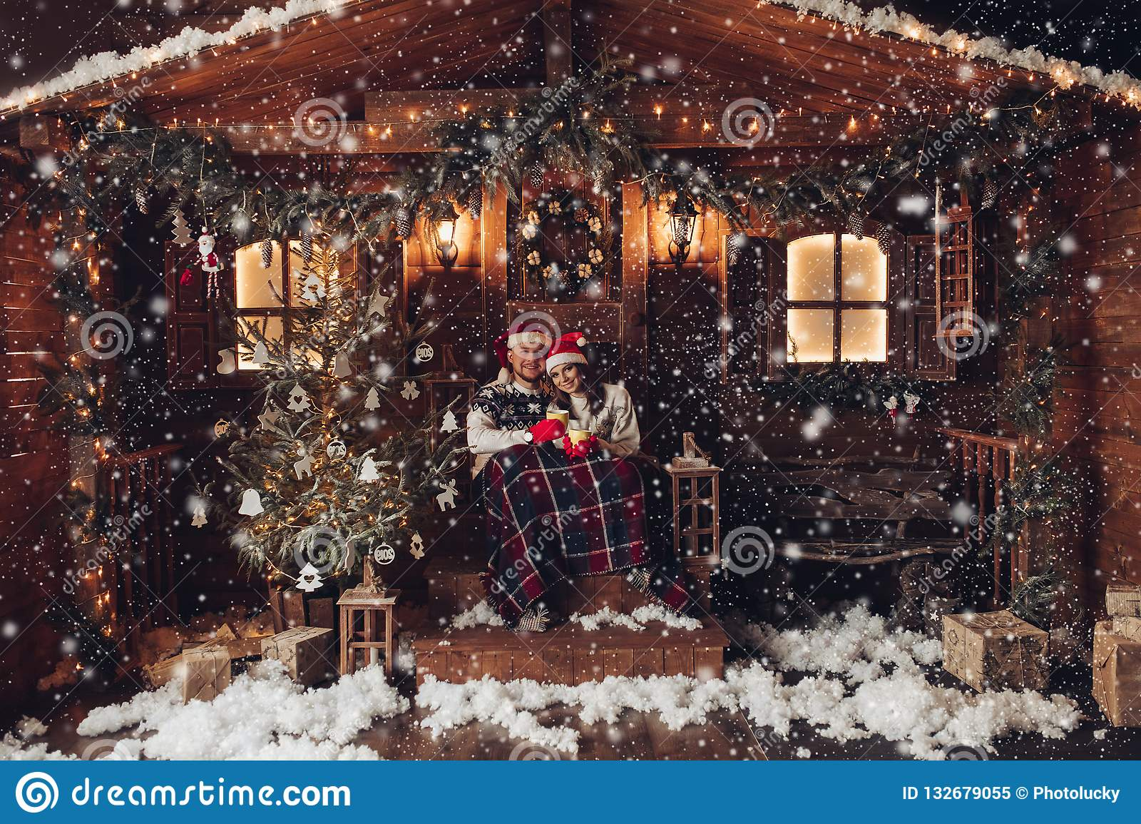 Christmas romance in Santa Claus hats beautiful house New Year`s atmosphere