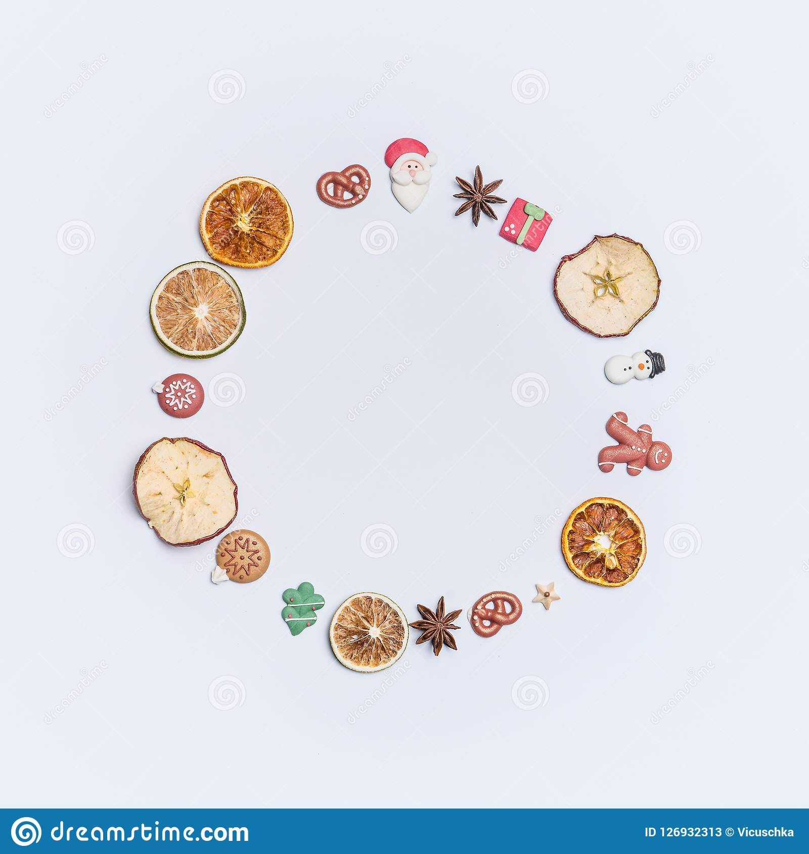 Christmas round circle fame or wreath made with dried fruits and anise stars and marzipan Christmas decor figures