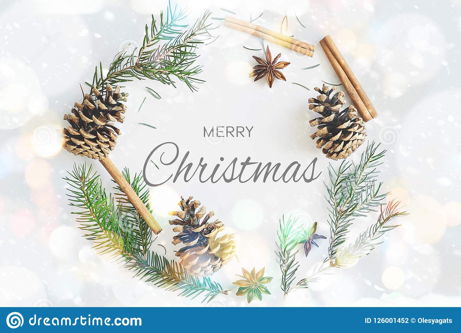 Christmas round frame wreath card with text merry christmas. Fir branches, cones, star anise, cinnamon on pastel blue bokeh backgr
