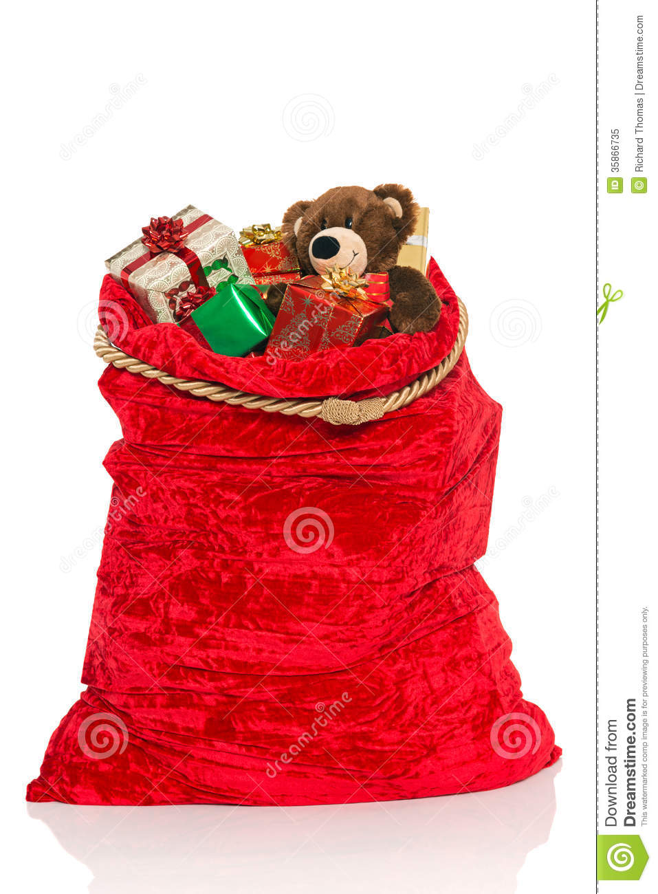 red Christmas sack full of gift wrapped presents and a handmade bear ...