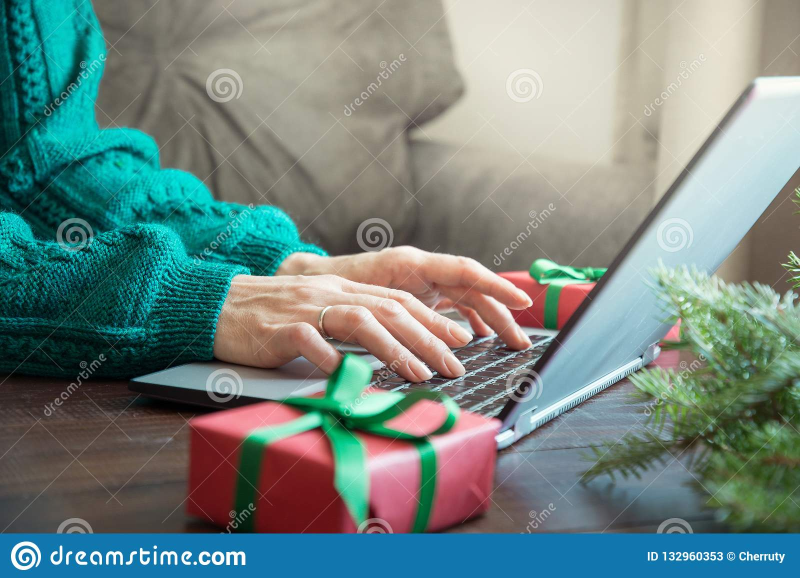 Christmas sales. Woman typing on laptop in home interior. Xmas concept. Planing holidays