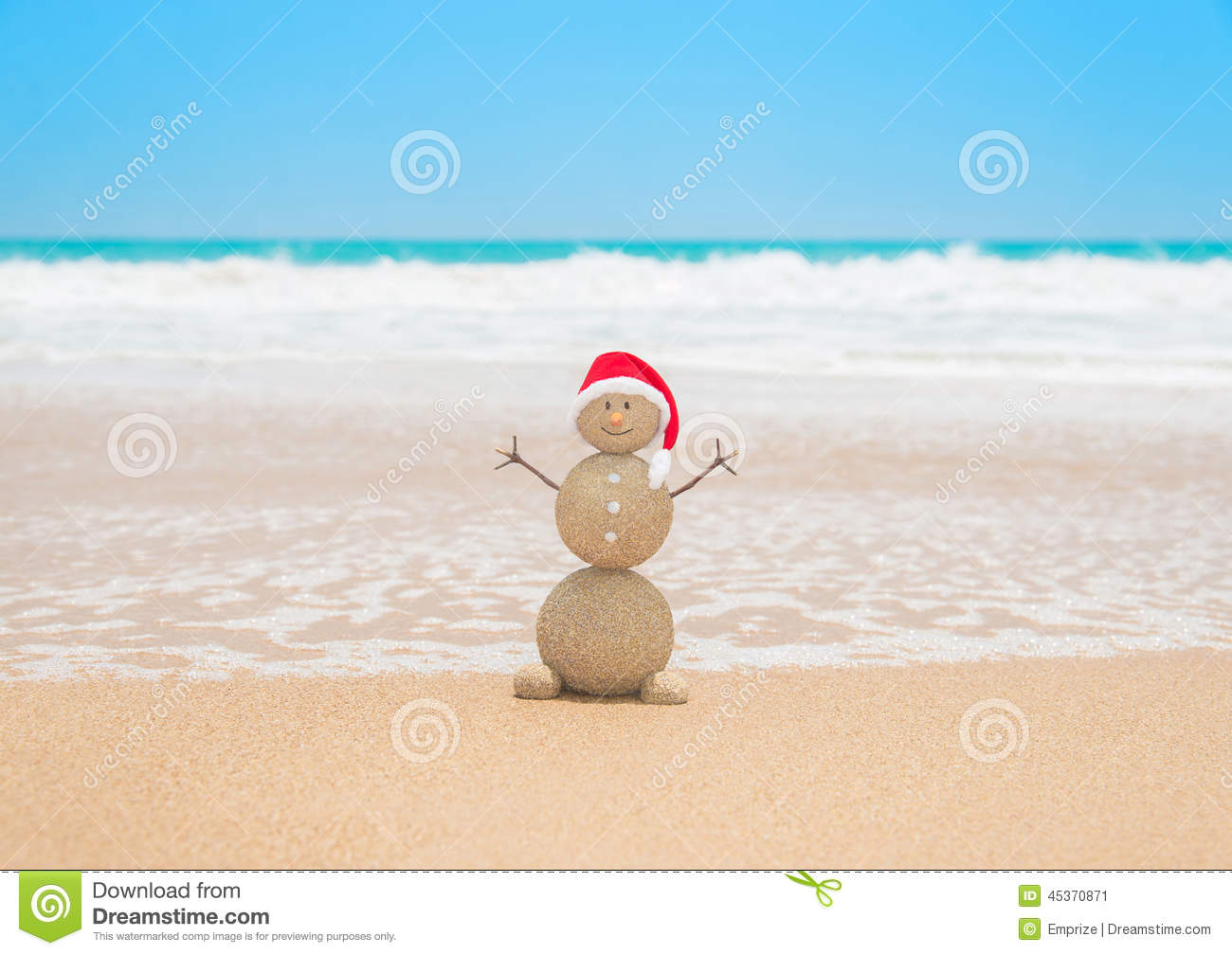 Christmas sandy snowman in red santa hat at tropical beach holiday