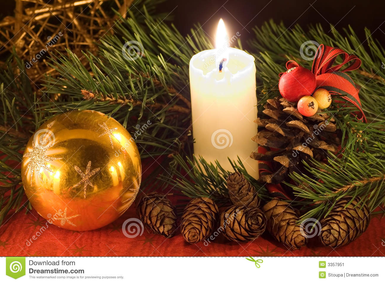 Christmas scene with golden ball white candle and cones in low light