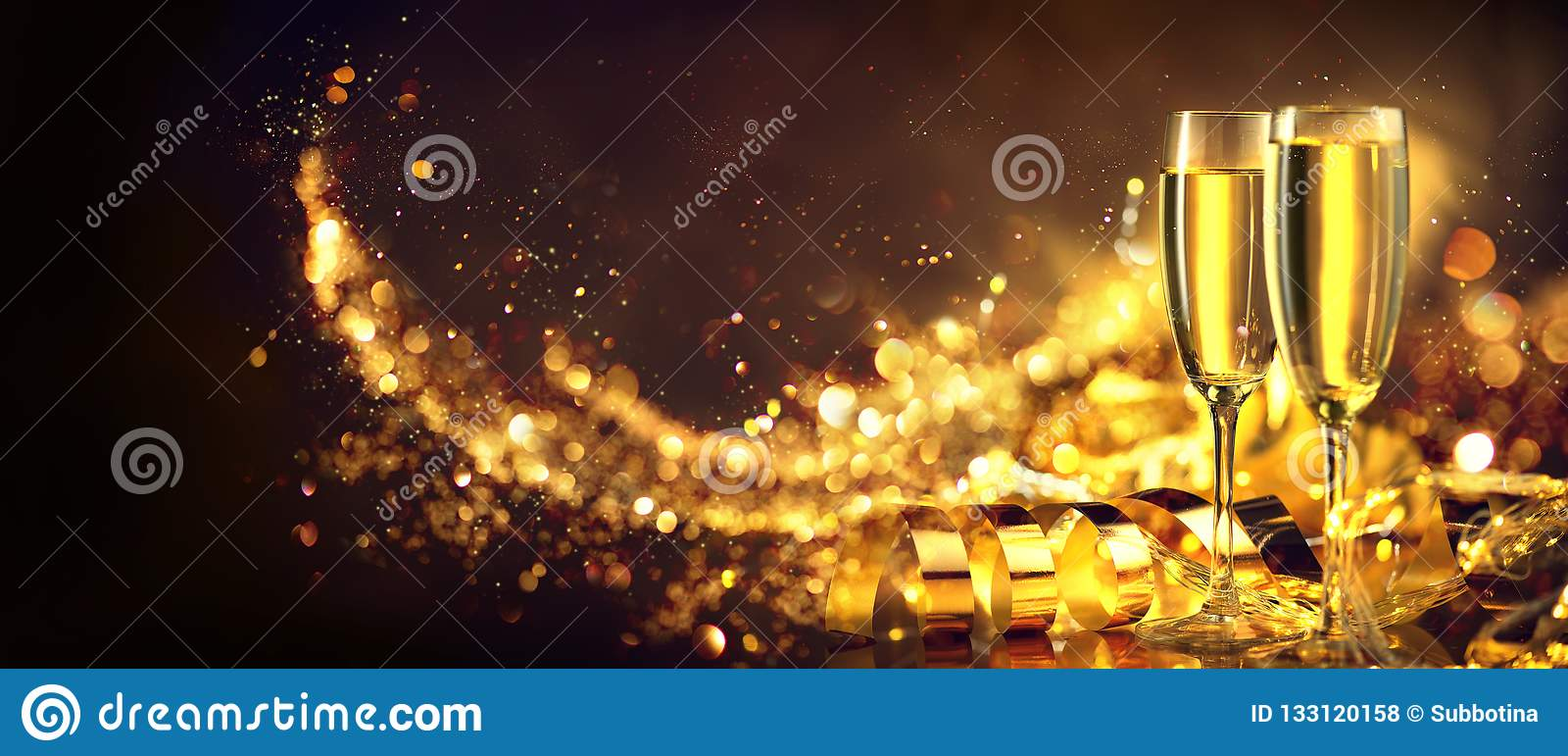 Christmas scene. Holiday champagne over golden glow background. Christmas and New Year celebration. Two flutes with sparkling wine