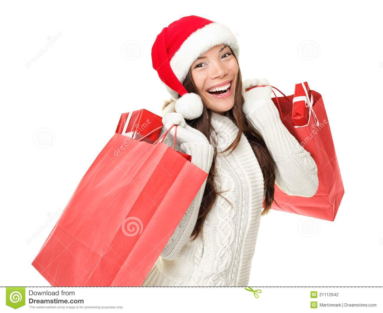 282bec21573ef Christmas shopping woman holding shopping bags with gifts. Happy and  smiling wearing red santa hat isolated on white background.