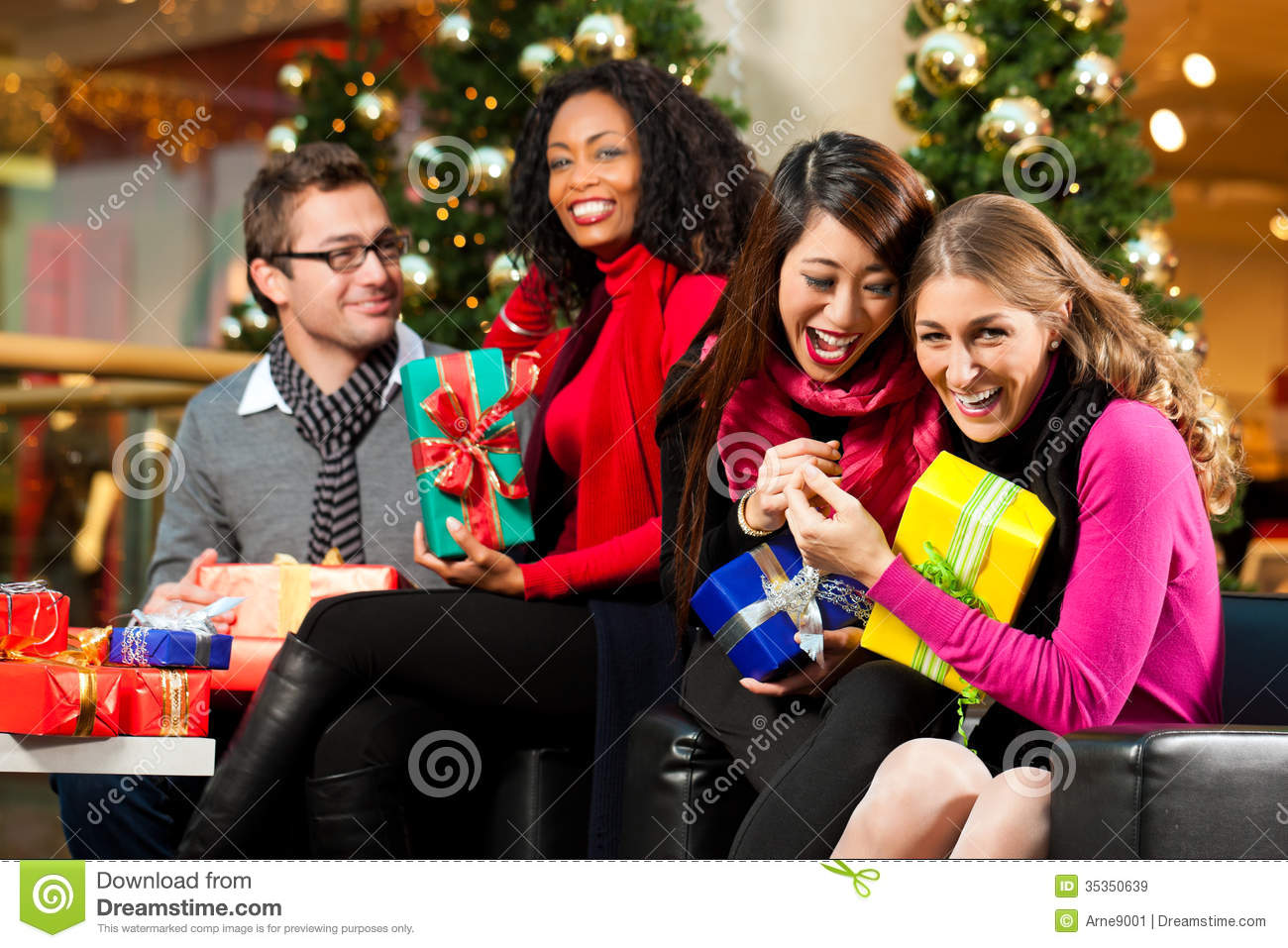 diversity group of four people caucasian black and asian sitting with christmas presents and bags in a shopping mall in front of a christmas tree with - Black People Christmas