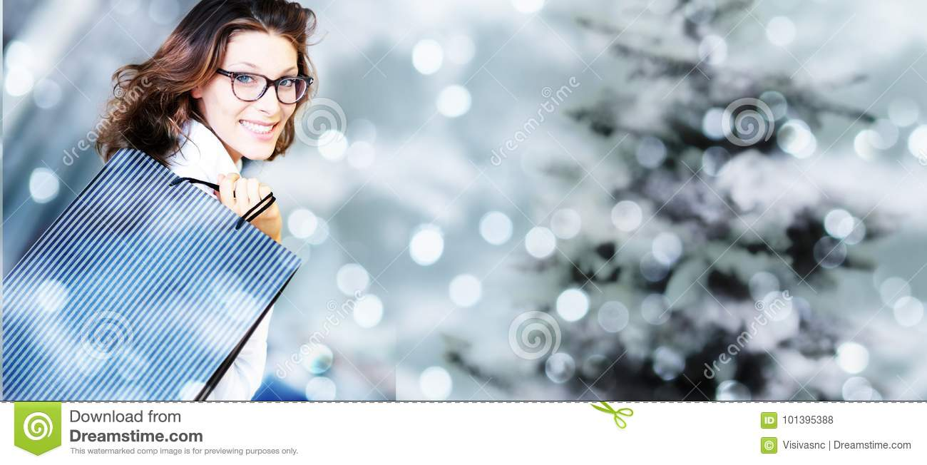 Christmas shopping, smiling woman with bags on blurred bright li