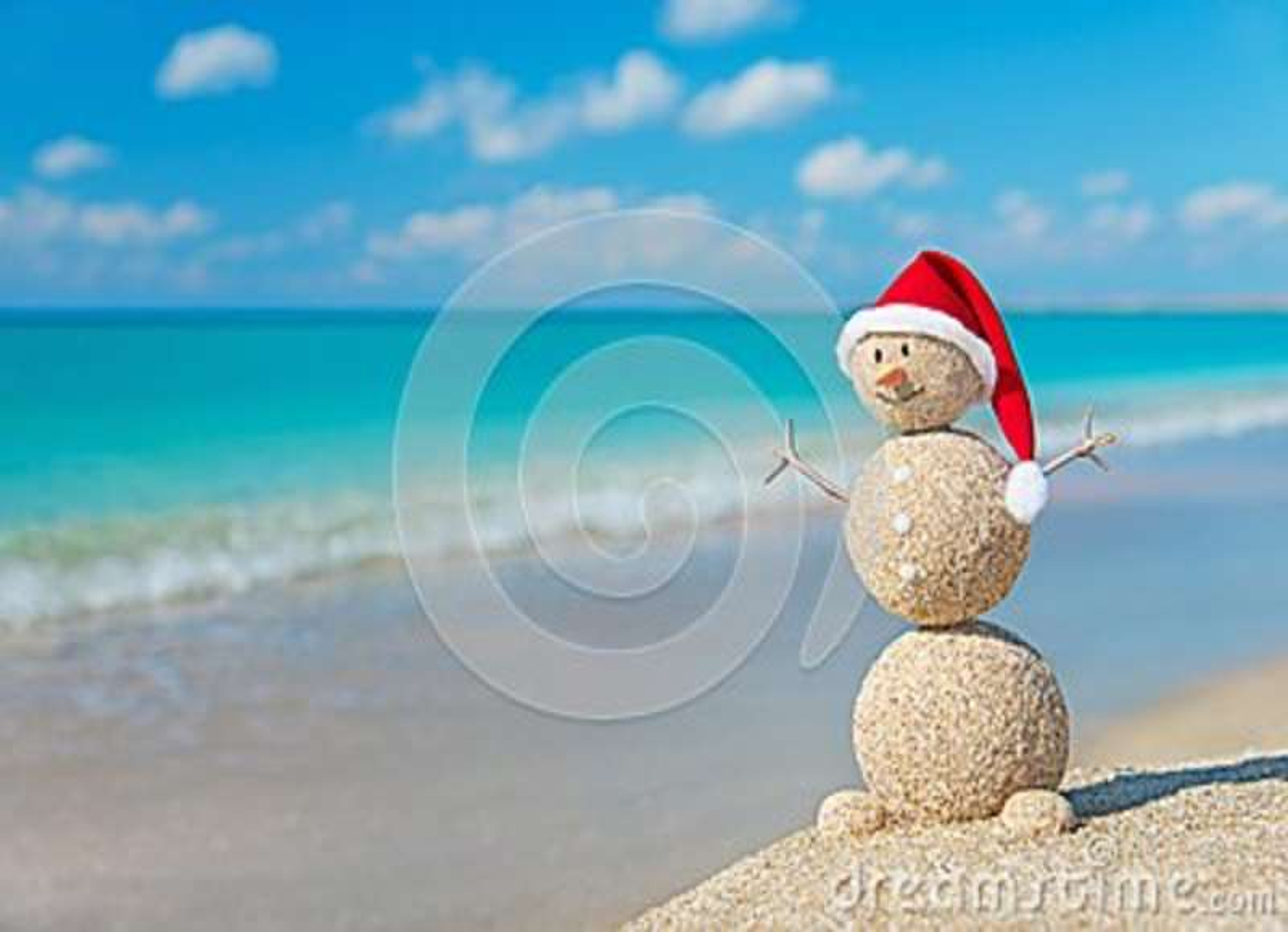 Christmas snowman in santa hat at tropical ocean beach