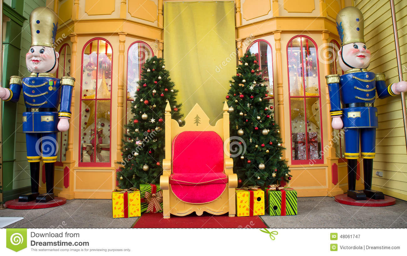 a landscape view of a christmas stage used to photograph santa claus with other people the stage has christmas decorations on it like the christmas tree - Christmas Stage Decorations
