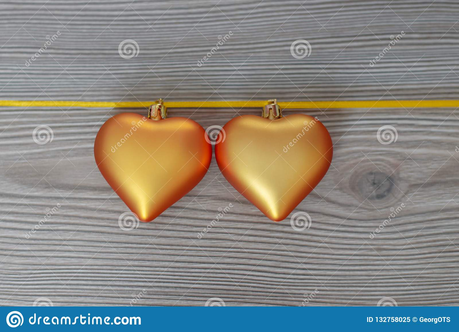 Christmas still life with love for loved ones, two golden hearts on one gold ribbon on a wooden background. Valentine`s Day Gift
