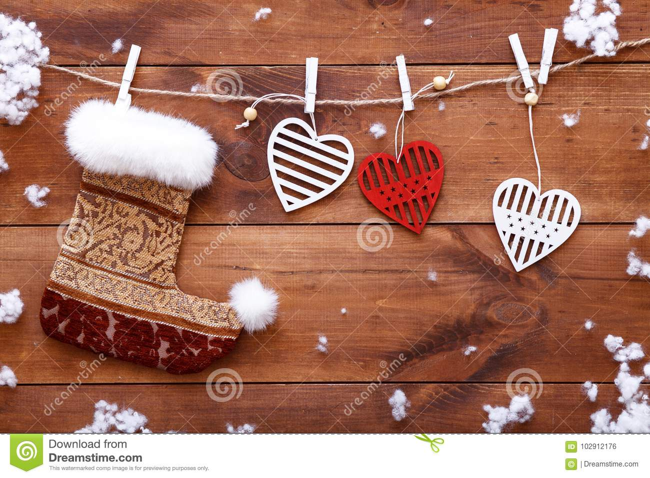 Christmas stocking, white red hearts hanging on brown wooden background, xmas valentines day card, copy space, top view