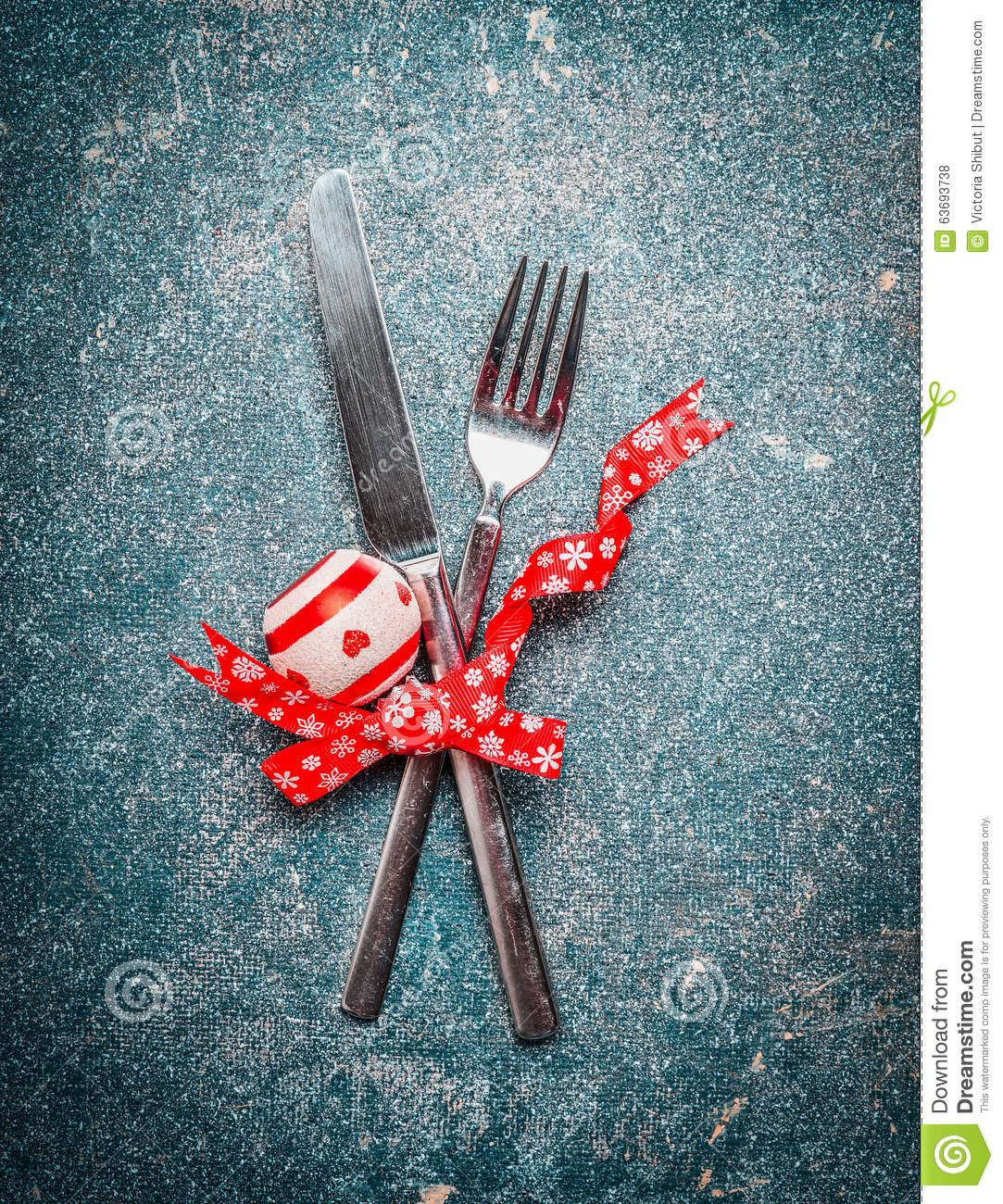 Christmas table place setting with fork, knife and red ribbon and ...