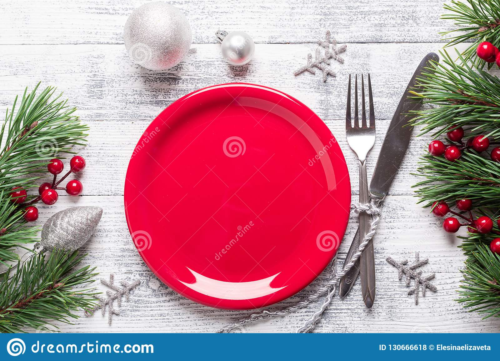 Christmas table setting with empty red plate, gift box and silverware on light wood background. Fir tree branch.
