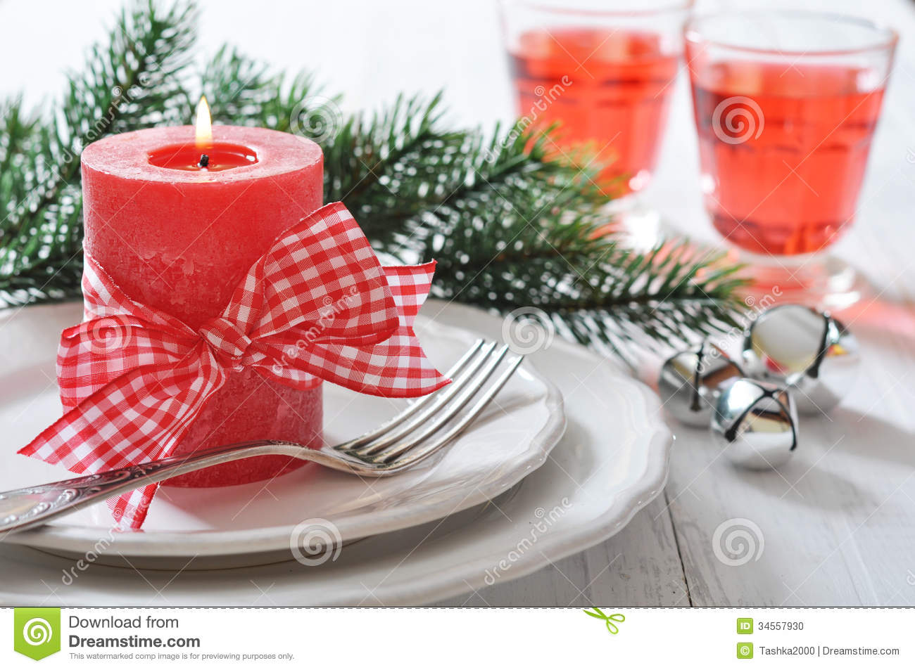 Christmas table setting with red candle and fir tree branch