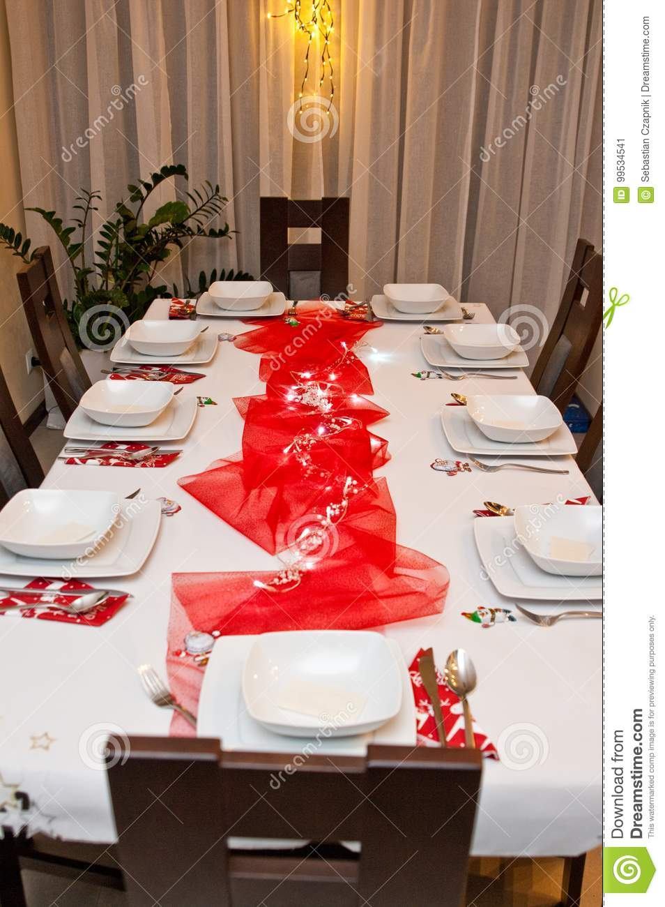 Christmas Table Setting With White Plates And Red Decorations Stock