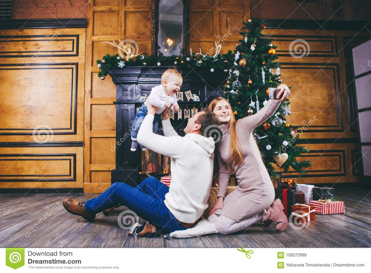 Christmas Theme. Father Throws The Son Of Blond One Year Old, Sit On ...