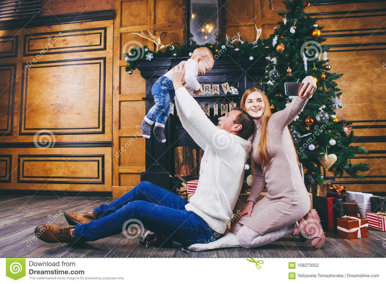 download christmas theme father throws the son of blond one year old sit on