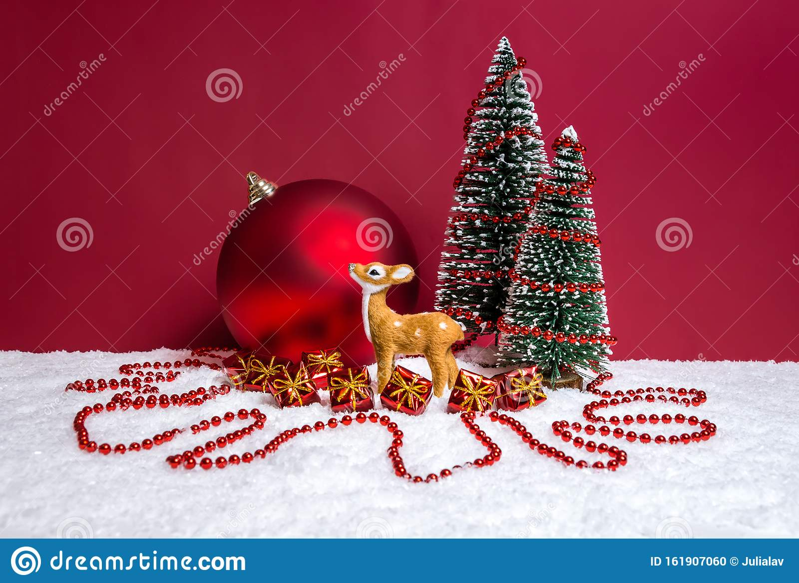 Christmas Theme With Miniature Reindeer Decorated Christmas Trees Presents And Big Bauble On Red Background Stock Photo Image Of Happy Evergreen 161907060