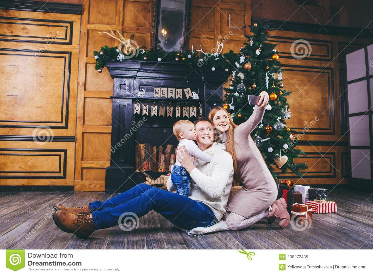 Christmas theme. young family with blond boy of one year sits on wooden floor against background of a Christmas tree with gifts an