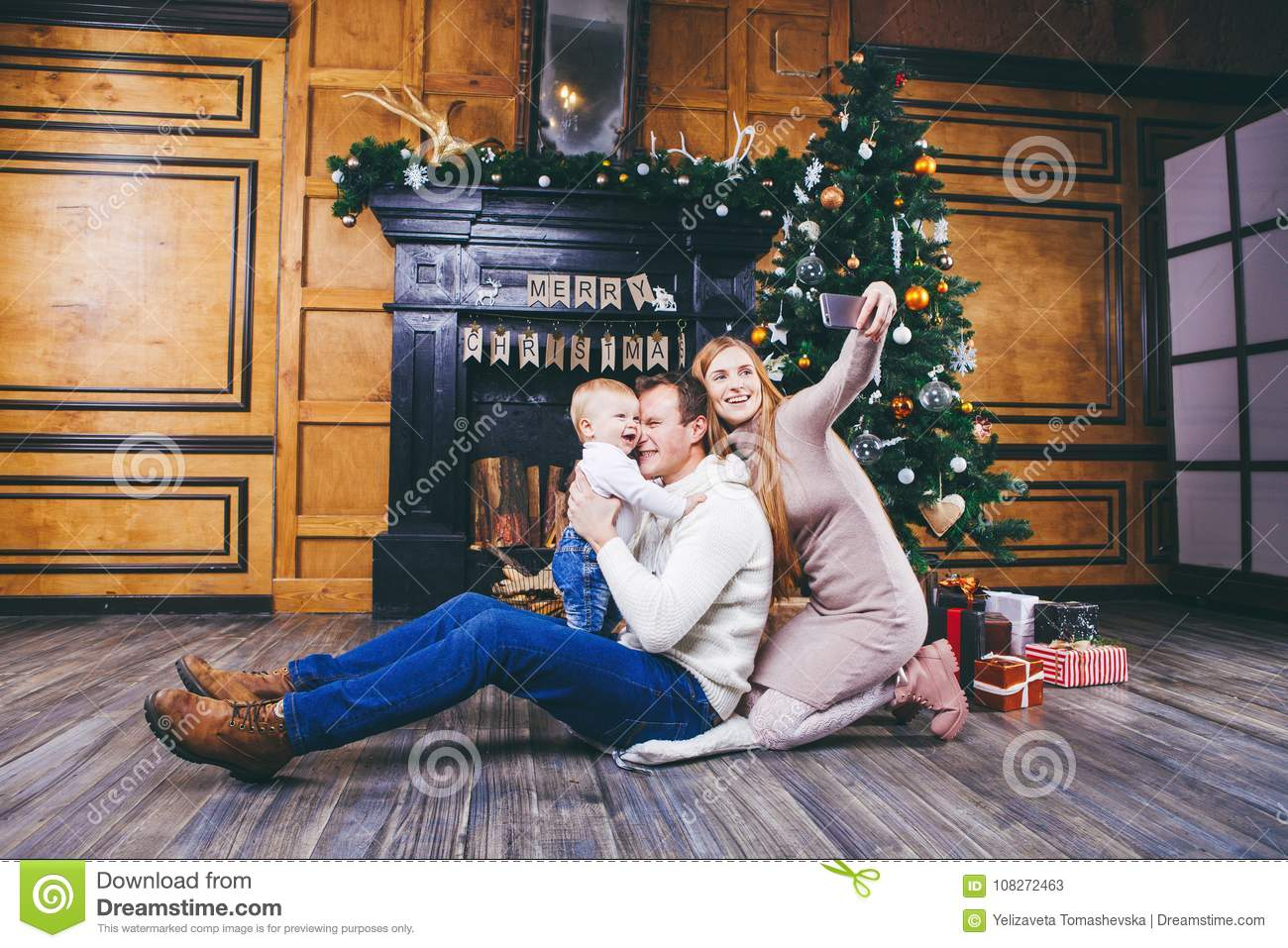 christmas theme young family with blond boy of one year sits on wooden floor against - Christmas By Myself This Year