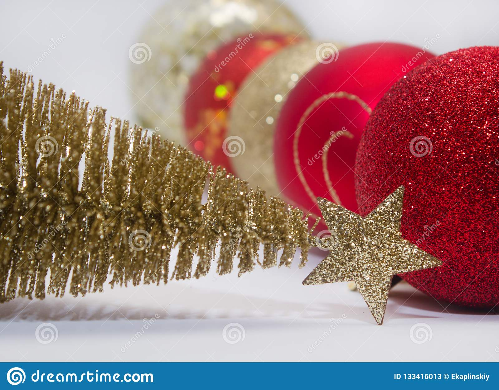 Christmas toy, a lot of shiny red, gold and silver balls and golden tree. New Year. On a gray background
