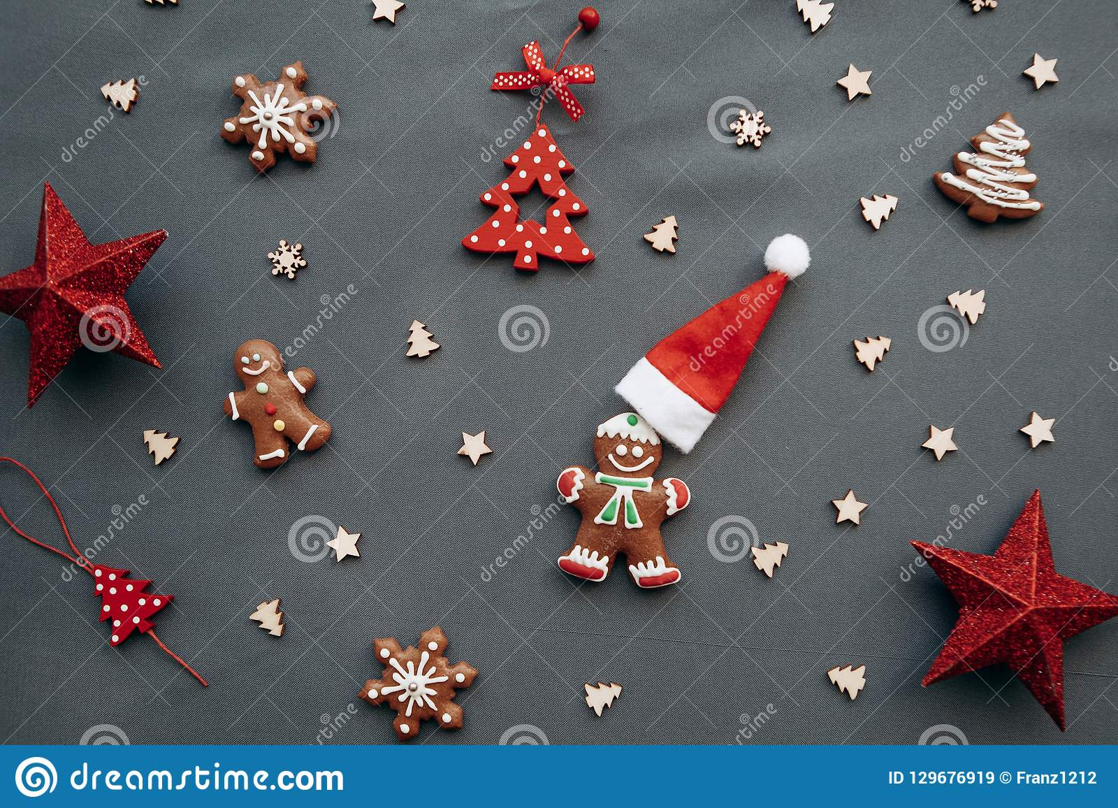 Christmas toys and gingerbread in the form of a traditional ginger man with a Santa Claus hat on a gray background.