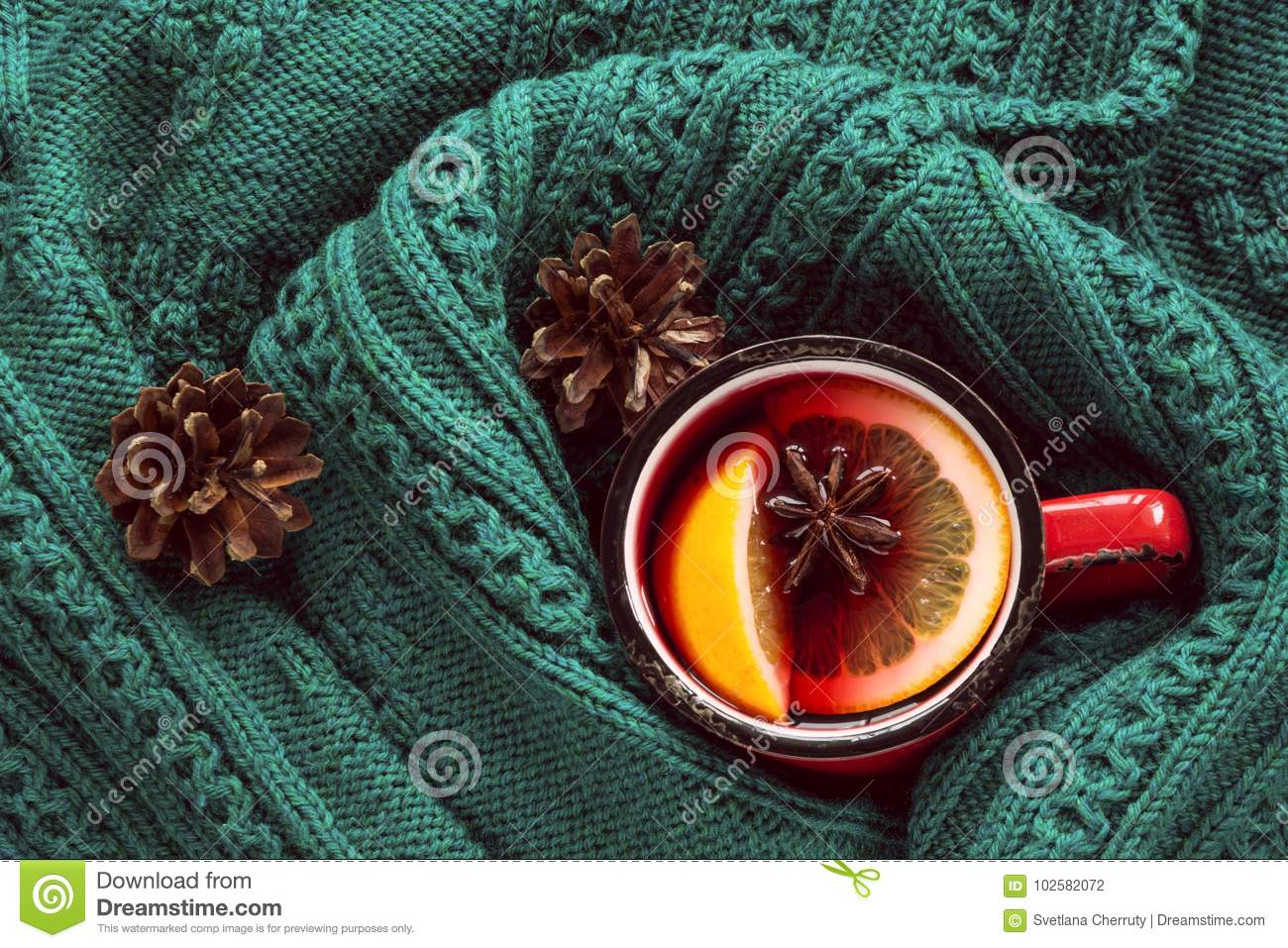Christmas traditional hot mulled wine in red mug with spice wrapped in warm green sweater.