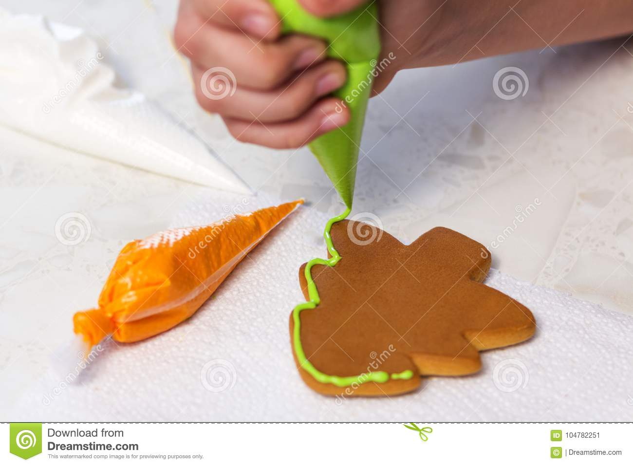 Baking holiday cookies. The child decorates homemade gingerbread in the form of a Christmas tree with green glaze.