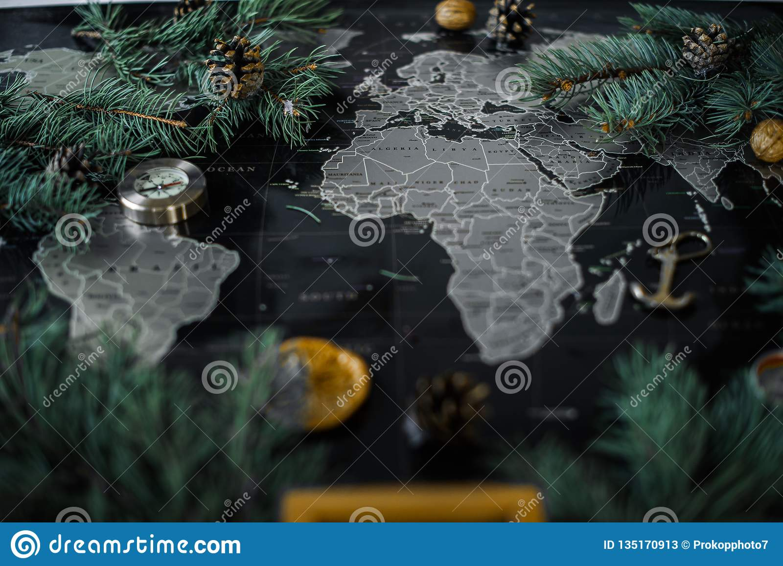 Christmas tree branches and compass on a black map