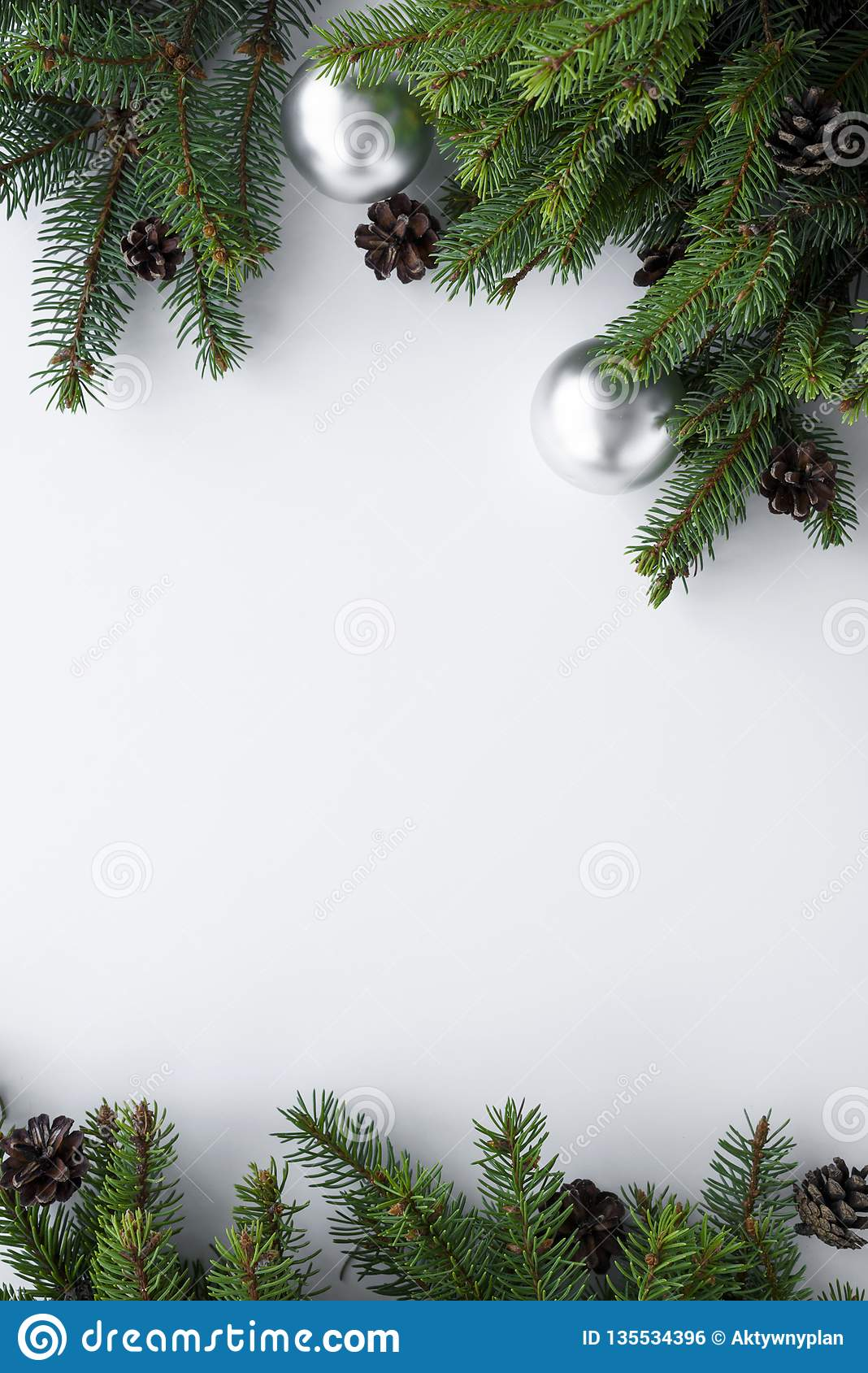 Christmas tree branches, cones and silver baubles as a vertical frame with copy space. Winter holidays composition