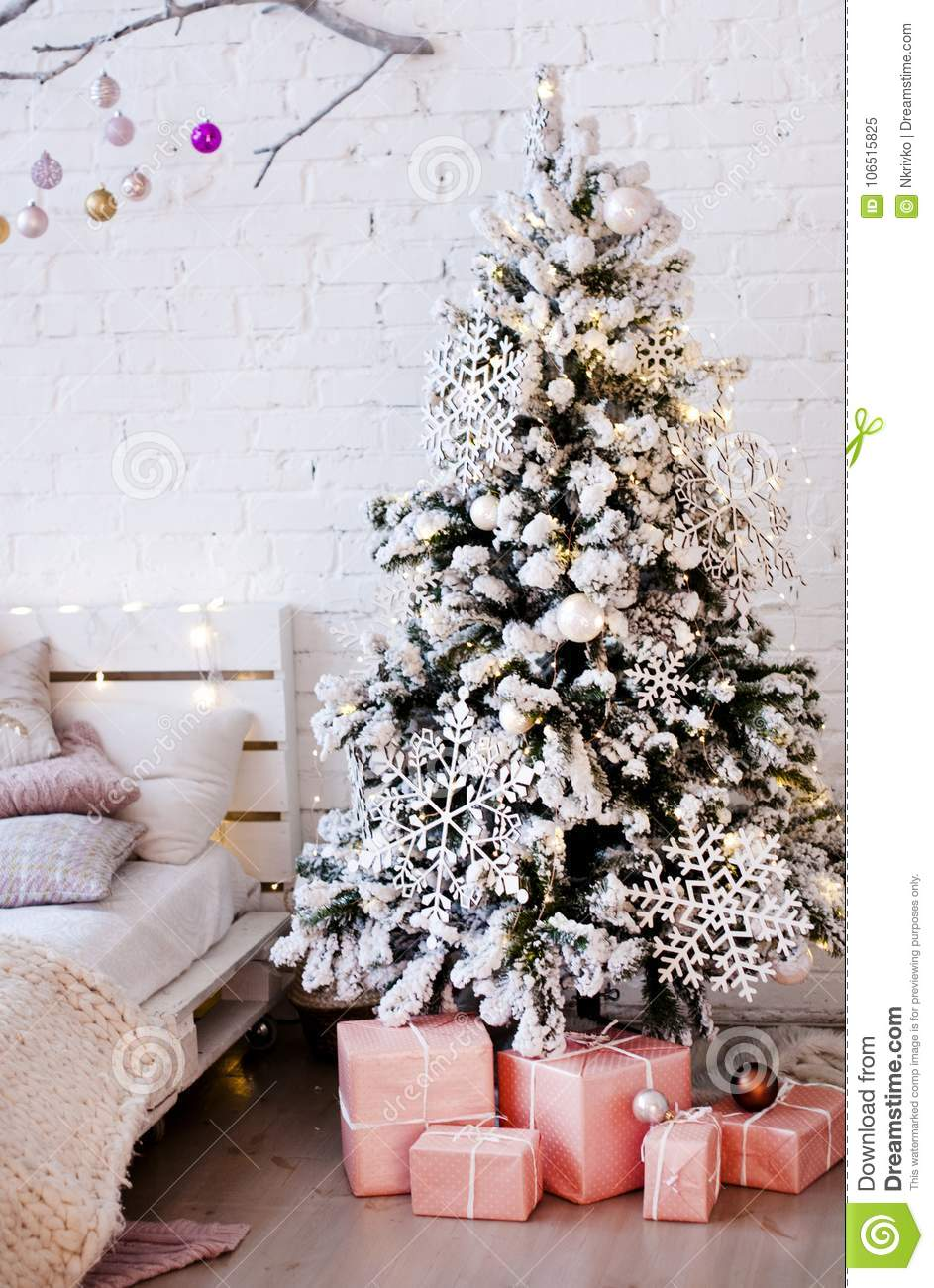 Christmas Tree Decorated With Large Wooden Snowflakes Near The Bed