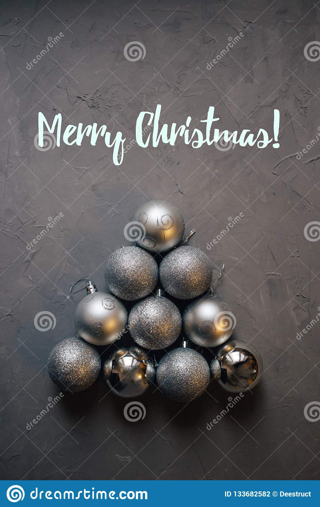 Christmas tree made by silver Christmas balls on the dark background, inscription merry Christmas