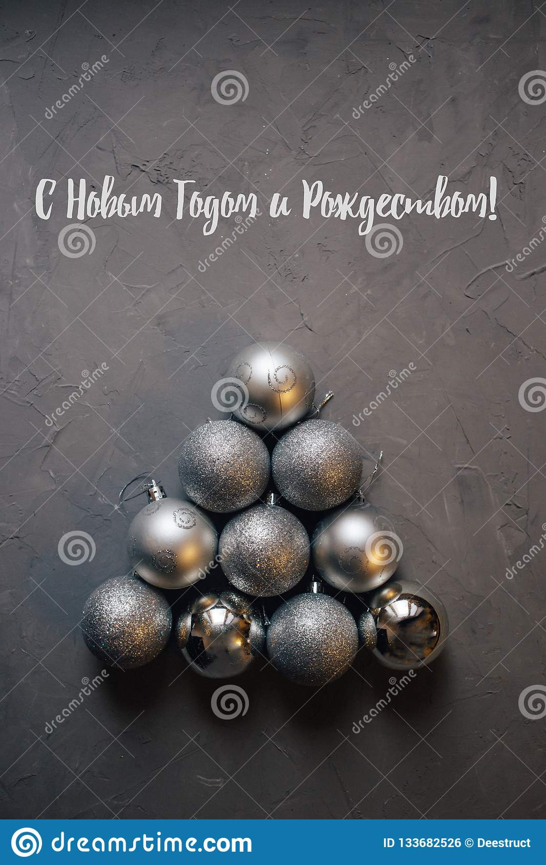 Christmas tree made by silver balls on the dark background, inscription in Russian: happy new year and merry Christmas