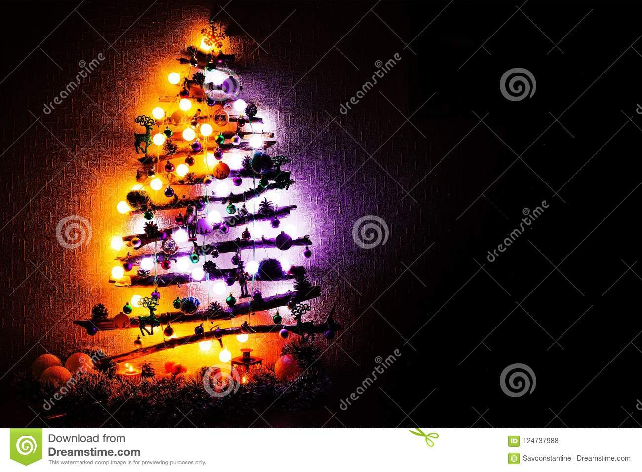 christmas tree made from twigs and sticks with purple and orange lights at night copy space